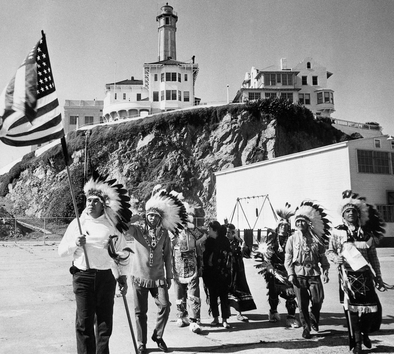 a group of Native Americans holding an American flag on a beach with buildings in the background (alcatraz)