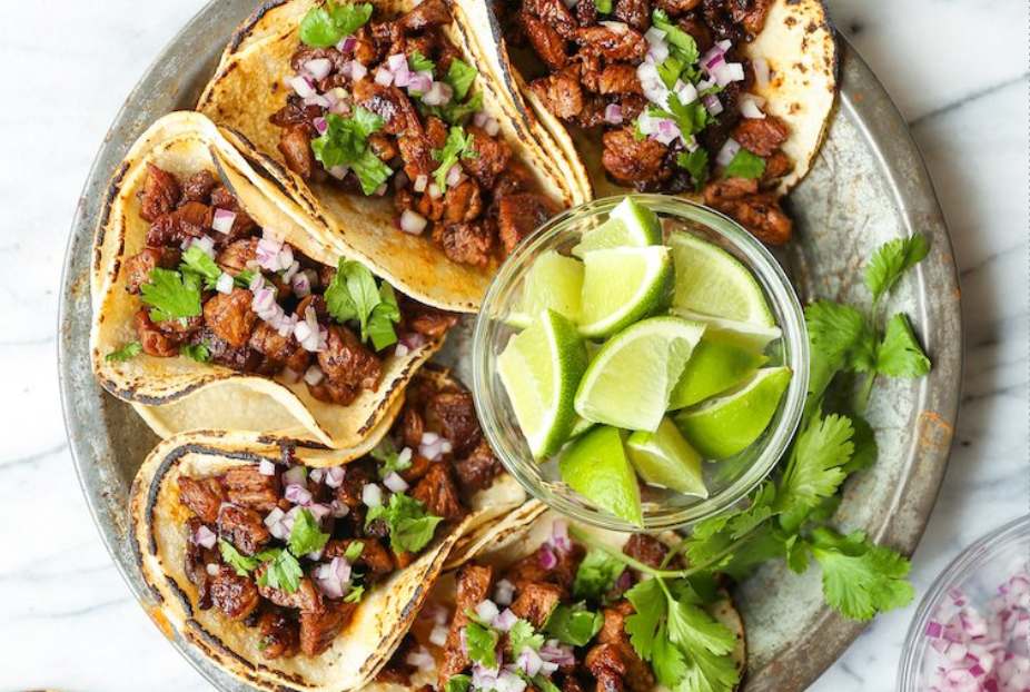 5 meaty tacos garnished with onions and cilantro and lime wedges