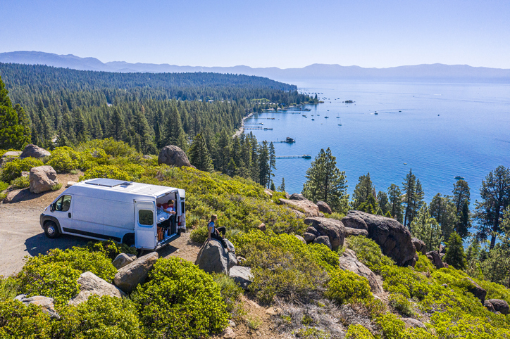 people parked in a beautiful location overlooking a body of water, living out of their van