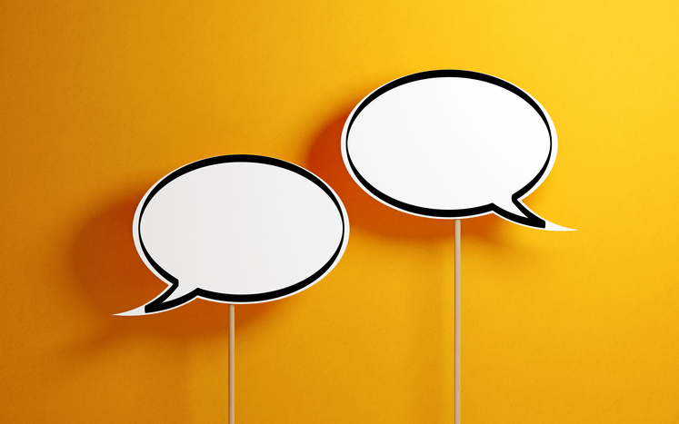 two white conversation bubbles with a yellow background