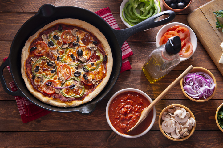 pizza in a skillet alongside bowls of ingredients like sauce and veggies