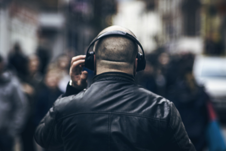 back of a man wearing headphones and a leather jacket