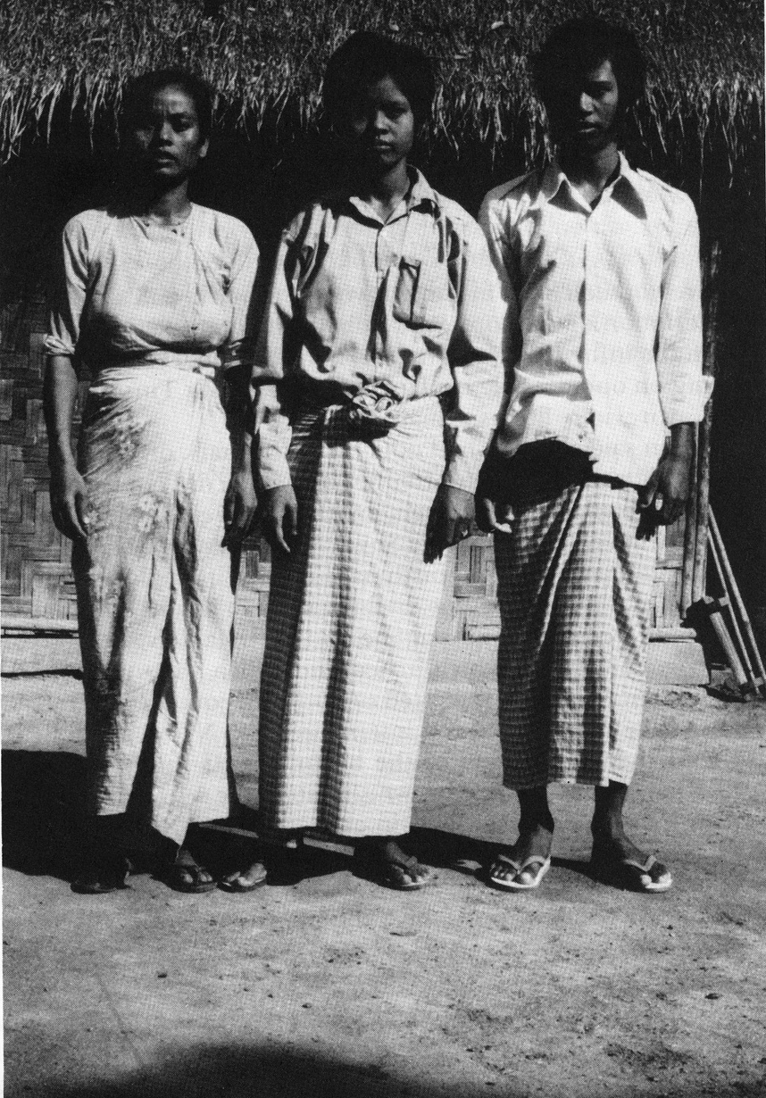 3 young people stand at attention shoulder to shoulder in front of a thatched hut