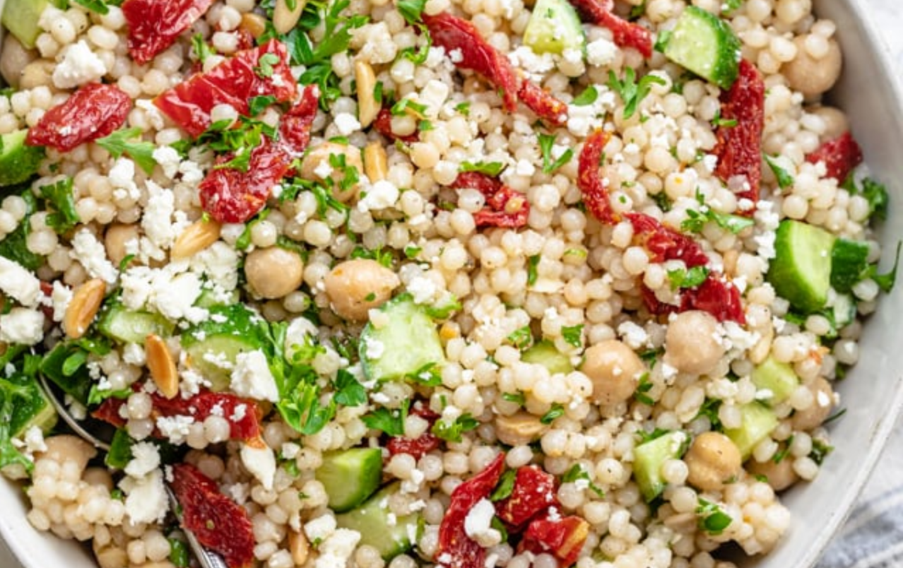 closeup of a cous cous salad with chickpeas and sundried tomatoes and cucumber