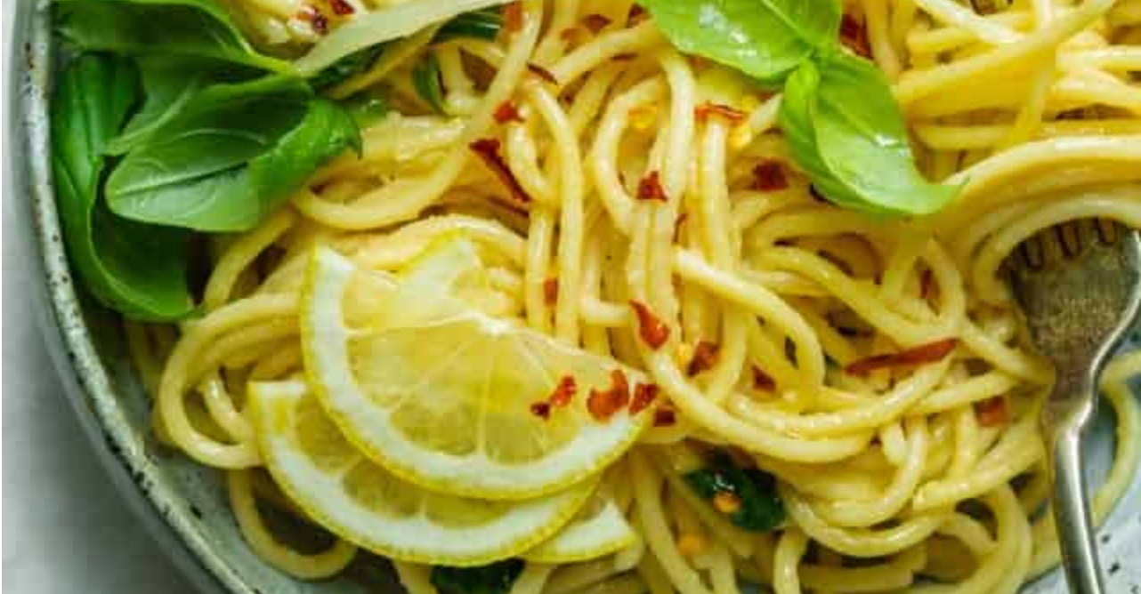 closeup of pasta noodles garnished with basic, pepper flakes and lemon
