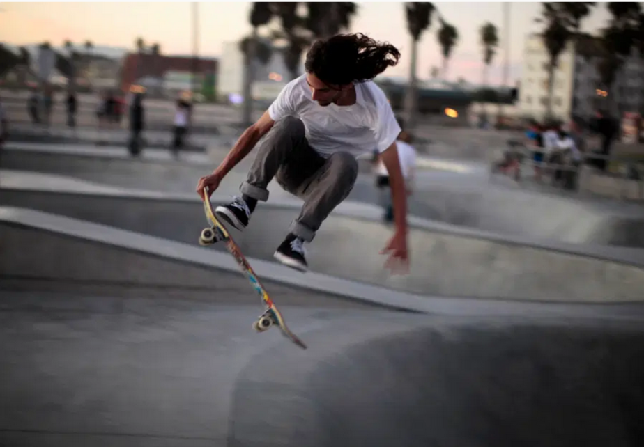 a guy performing aerial tricks on a skateboard in a skatepark