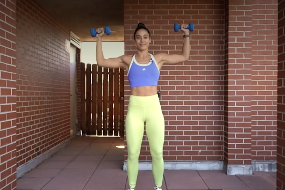 person with feet shoulder-width apart, knees slightly bent, holding a dumbbell in each hand, arms bent at 90-degree angles, elbows wide and in line with shoulders, palms facing forward.