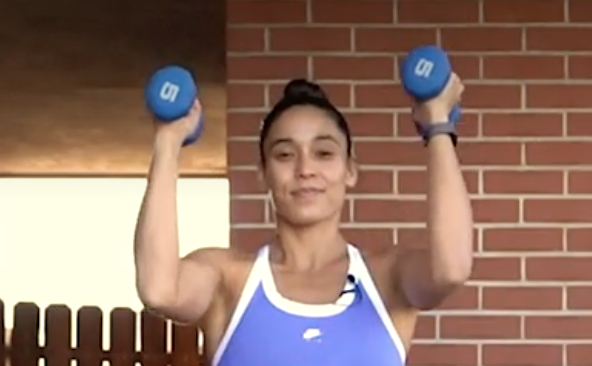 person standing with feet under shoulders, soft bend in knees, holding a pair of dumbbells at chin height, arms narrow in front of body and bent, palms facing inward