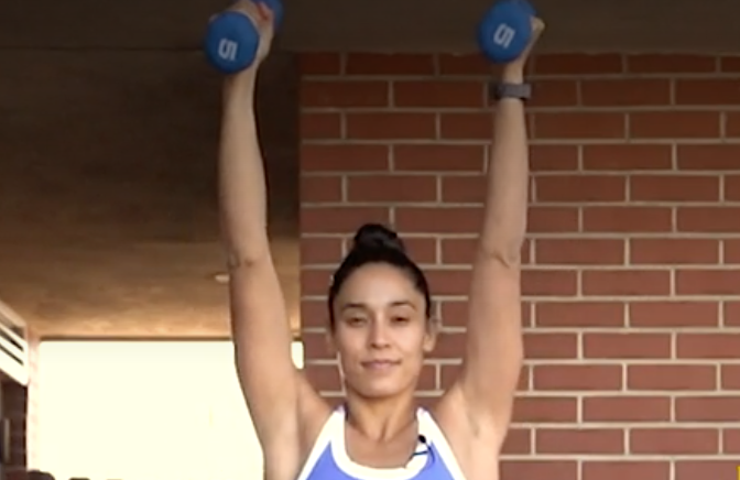person standing with feet under shoulders, soft bend in knees, holding a pair of dumbbells straight up, arms narrow in front of body and bent, palms facing inward
