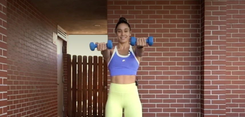 person standing with feet shoulder-width apart holding a dumbbell in each hand, arms straight, palms facing up, weights extended to shoulder level