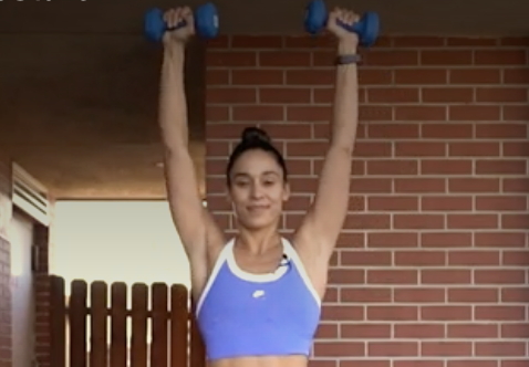person pressing the weights overhead, rotating palms away from body.