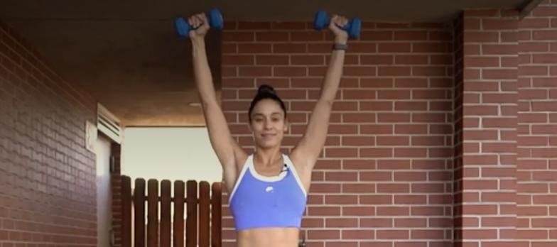 person with feet shoulder-width apart, knees slightly bent, holding a dumbbell in each hand, arms extended straight up