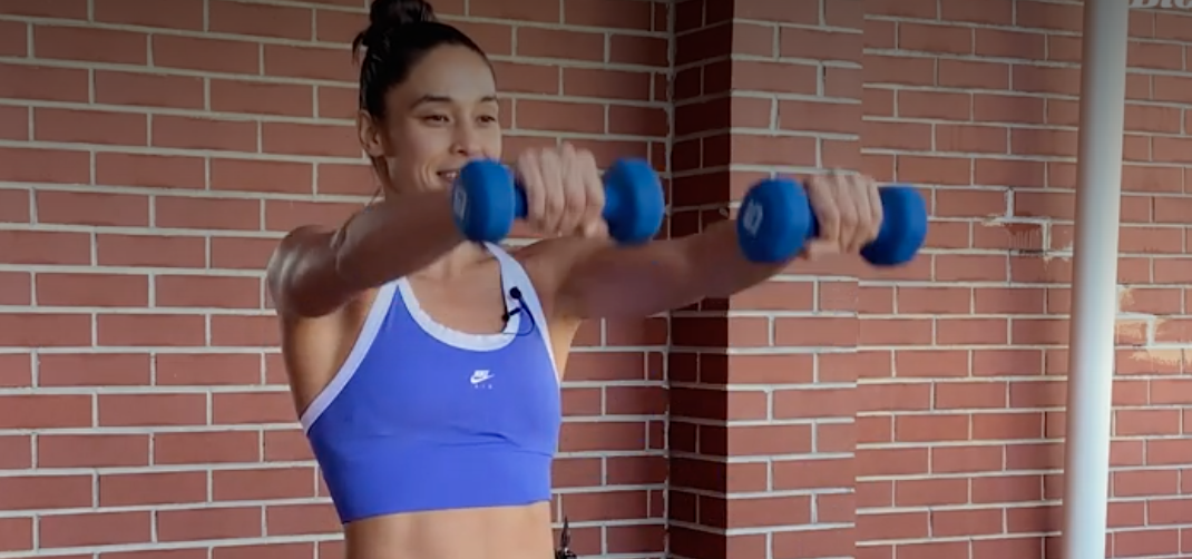 person standing with feet shoulder-width apart holding a dumbbell in each hand, arms straight, palms facing body, weights held straight up at shoulder height