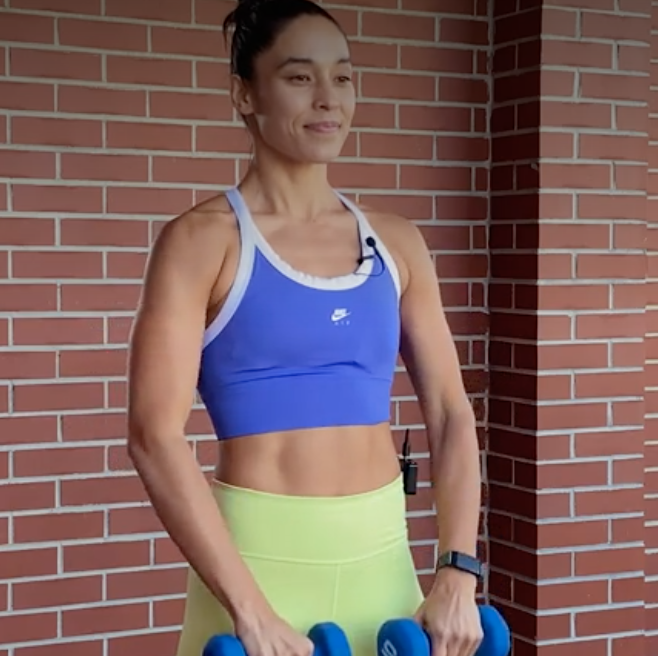 person with feet shoulder-width apart, holding a dumbbell in each hand, palms facing toward body, and weights touching quads.