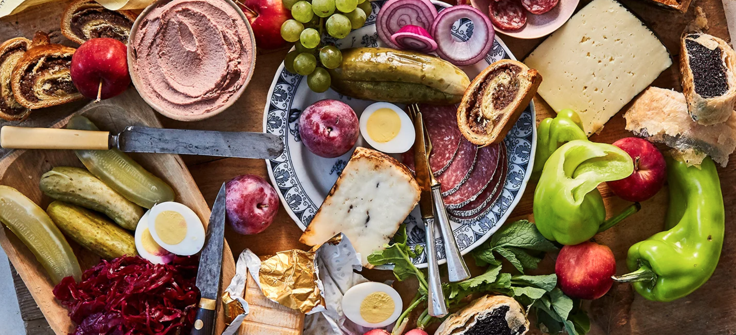large platter of fruits, veggies, meats, pastry, cheese, dip and more
